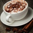 Coffee cup and beans, cinnamon sticks, nuts and chocolate on woo — Стоковая фотография