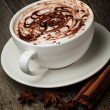 Coffee cup and beans, cinnamon sticks, nuts and chocolate on woo - Foto Stock