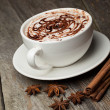 Coffee cup and beans, cinnamon sticks, nuts and chocolate on woo — Stockfoto