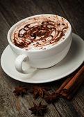 Kaffekopp och bönor, kanelstänger, nötter och choklad på woo — Stockfoto
