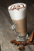 Taza de café con leche y frijoles, palitos de canela, nueces y chocolate en woo — Foto de Stock
