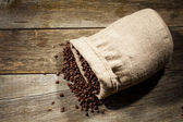 Burlap sack of coffee beans against dark wood background — Stock Photo