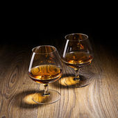 Two goblets of brandy warmed by the glow of the lights on wooden — Stock Photo
