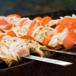 Pieces of meat roasting at skewers, named shashlik — Stock Photo