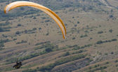 Orange paraglider above the valley — Stock Photo