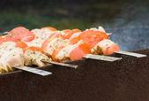Shish kebab roasting on skeweres — Stock Photo