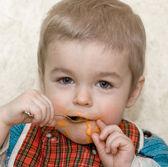 Cute little boy eating squash — Stock Photo