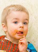 Cute little boy licking his lips during a meal — Stock Photo