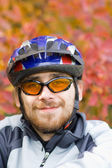 Young smiling bicycler on the background of autumn leaves — Stock Photo