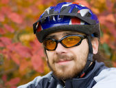 Young bicycler on the background of autumn leaves — Stock Photo