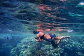 Woman in bikini between fish — Stock Photo