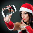Beautiful sexy girl wearing santa claus clothes with smartphone — Stock Photo