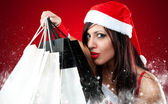 Girl wearing santa claus clothes with shopping bag — Stock Photo
