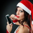 Girl wearing santa claus clothes with smartphone — Stock Photo