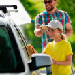 Carwash - young girl helping father to wash car. — Foto Stock