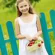 Strawberry time - young girl with picked strawberries in the gar — Stock Photo
