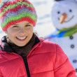 Winter fun, happy kid playing with snowman — Stockfoto