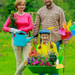 Gardening - happy family with wheelbarrow working in the garden — Stock Photo #31302077