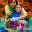 Gardening - lovely girl with mother working in flowers garden — Photo