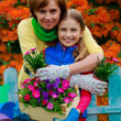 Gardening - lovely girl with mother working in flowers garden — Foto de Stock