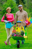 Gardening - happy family with wheelbarrow working in the garden — Stock Photo