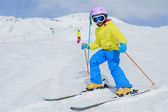 Skiing, skiers on ski run - child skiing downhill — Stock Photo