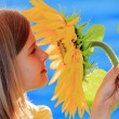 Girl and sunflower - beautiful girl is smelling sunflower — Stock Photo