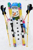 Winter, snow and fun - happy snowman with ski equipment — Stock Photo