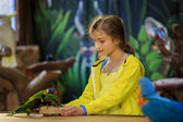 Trip to the Zoo - girl feeds a parrots at the Zoo — Stock Photo