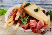 Italian prosciutto di Parma with grissini, Grana Padano — Stock Photo