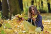 Podzimní zábavu - krásná dívka má zábavu v podzimním parku — Stock fotografie
