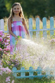 Summer fun, girl watering flowers — Stock Photo