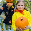 Scarecrow and happy girl in the garden - Autumn harvests — Stock Photo #46827907