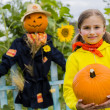 Scarecrow and happy girl  in the garden - Autumn harvests — Stock Photo #46827929