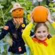 Scarecrow and happy girl  in the garden - Autumn harvests — Stock Photo #46827933