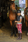 Horse and lovely equestrian girl in the stable — Stock Photo