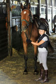 Horse and lovely equestrian girl in the stable — Photo