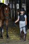 Horse and lovely equestrian girl in the stable — Stockfoto