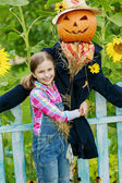 Scarecrow and happy girl  in the garden — Stock Photo