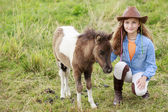 Little foal and girl - cute girl takes care of the pony foal — Stock Photo