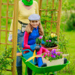 Gardening - lovely girl with mother working in flowers garden — Stock Photo #47077655