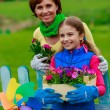 Gardening - lovely girl with mother working in flowers garden — Stock Photo #47078853
