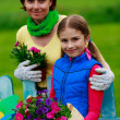 Gardening - lovely girl with mother working in flowers garden — Stock Photo #47078855