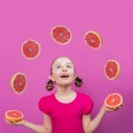 Grapefruit, healthy eating - a young girl juggling grapefruits — Stock Photo #47085669