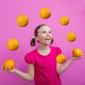 Grapefruit, healthy eating - a young girl juggling grapefruits — Stock Photo
