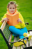 Young girl with headphones reading a book — Foto Stock