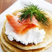 Gourmet smoked salmon and cream cheese blinis — Stock Photo