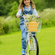 Spring cycling - girl with flowers riding a bike — Stock Photo #47335925