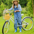 Spring cycling - girl with flowers riding a bike — Stock Photo #47335959