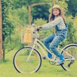 Spring cycling - girl with flowers riding a bike — Stock Photo #47335961